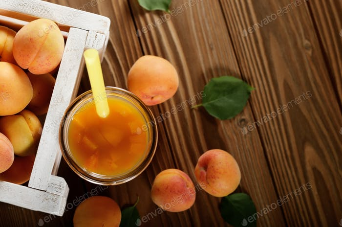 Apricot smoothie in mason jar and crate on wooden table. Top vie