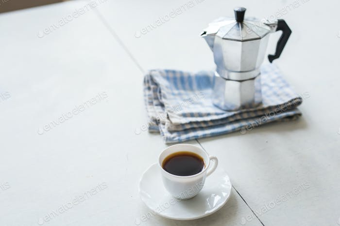 Cup of coffee, coffee kettle on a white table