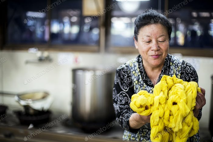 Japanese woman standing in a textile plant dye workshop, holding piece of bright yellow fabric.
