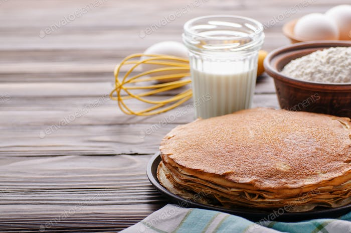 Stack of French crepes in frying pan on wooden kitchen table wit