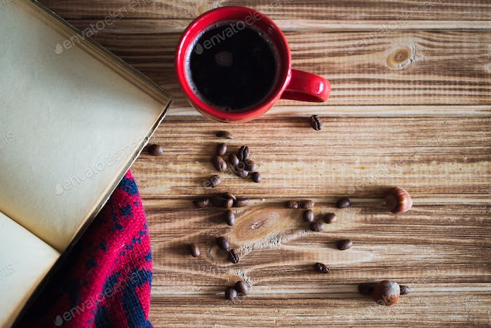 Cup of coffee and books on tablecloth on wooden background