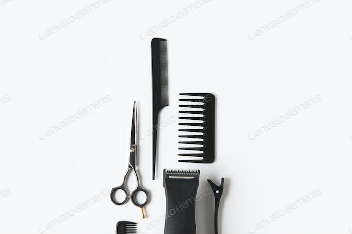 flache Lage mit Haarmaschine und Friseurwerkzeugen, auf weiß