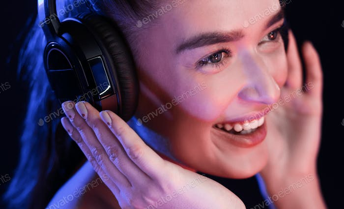 Young woman enjoying music in headset, posing in studio