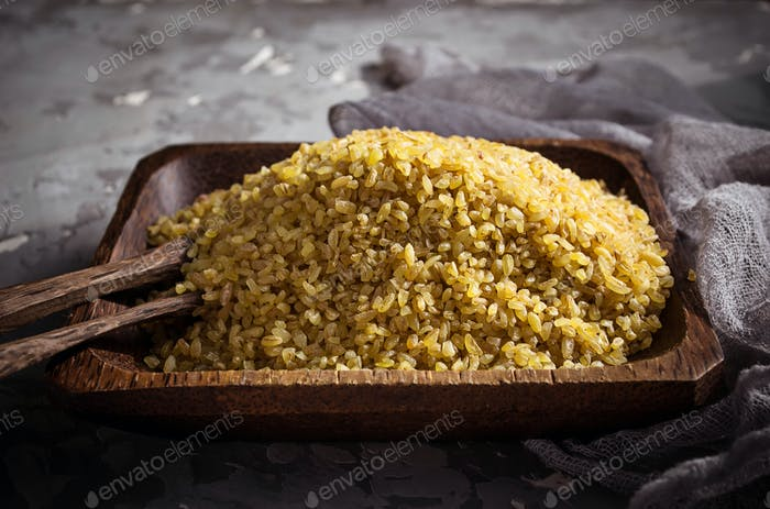 Bulgur wheat grains in a wooden bowl
