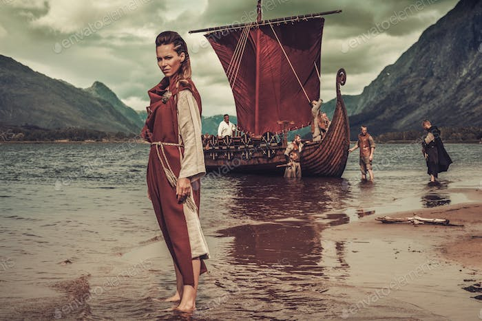 Viking woman standing near Drakkar on seashore