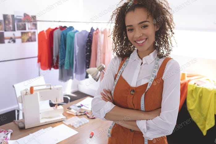 Female fashion designer standing at table in design studio