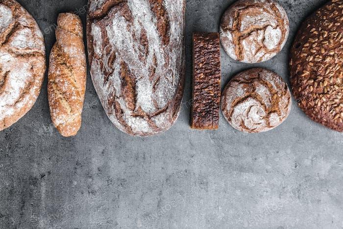 Köstliches frisches braunes Brot auf hölzernem Hintergrund