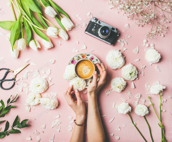 Female hands holding cup of coffee, flowers and film camera