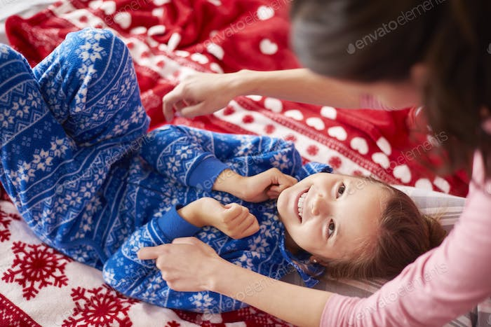 Girl with mom playing together in the bed