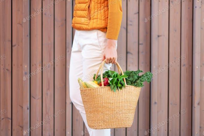 Zero-Waste Konzept mit Kopierraum. Frau hält Strohkorb mit Gemüse, Produkte. Öko