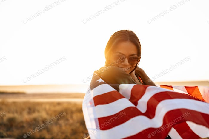 Nice happy girl smiling while posing with american flag on nature