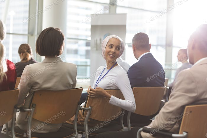 Businesswoman interacting with his colleague during seminar in office building