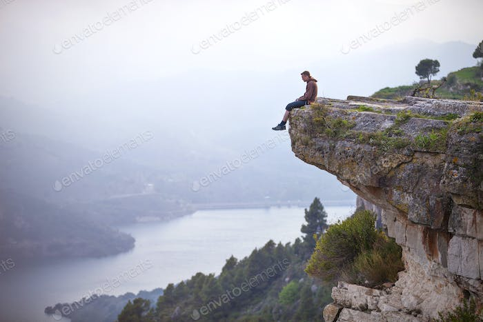 Young man sitting on edge of cliff and looking at river below