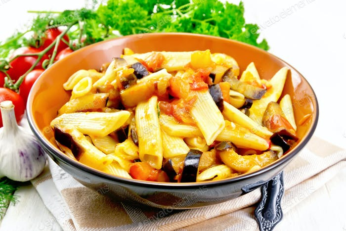 Pasta penne with eggplant and tomatoes on towel