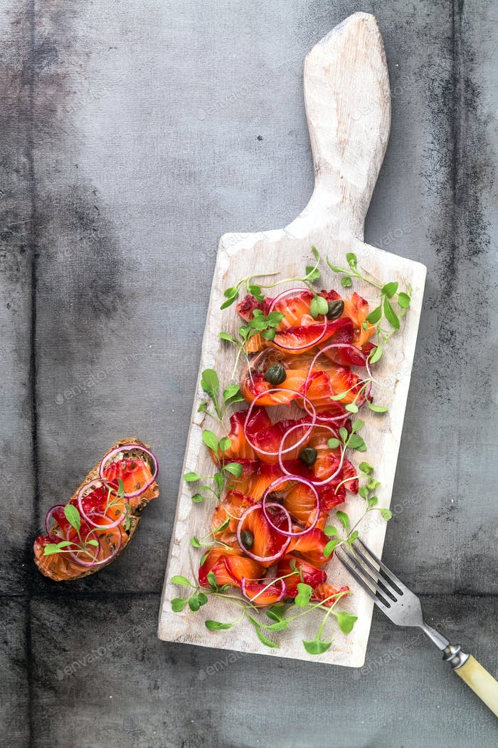 Sliced marinated salmon on wooden board