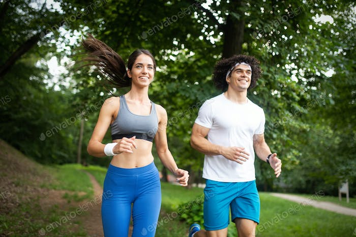 fitness, sport, friendship and lifestyle concept - smiling couple exercising outdoors