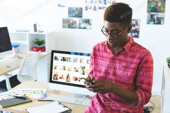 Front view of young African-American graphic designer using mobile phone at desk in office