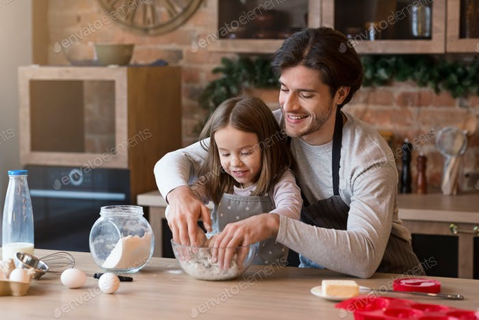 Father and daughter making pastry in kitchen together, kneading dough