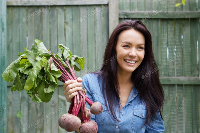 Smiling vegetarian woman holding bunch of beetroots