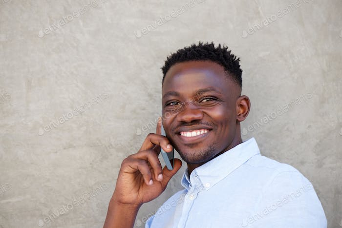 handsome young black man making a phone call by wall
