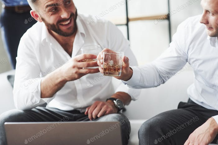 Two colleagues celebrating good deal in their business by drinking alcohol