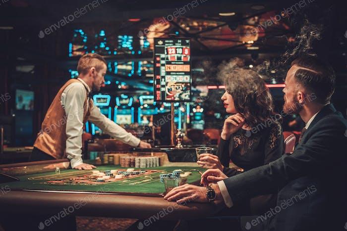 Upper class couple gambling in a casino