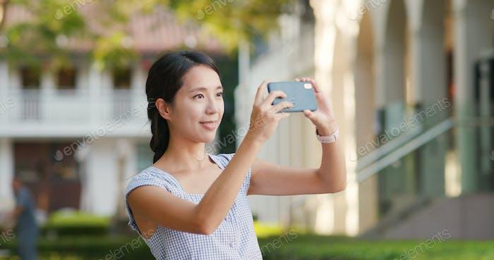 Frau, die Foto auf dem Handy im freien