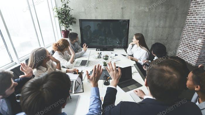 Businesspeople watching online presentation on tv screen