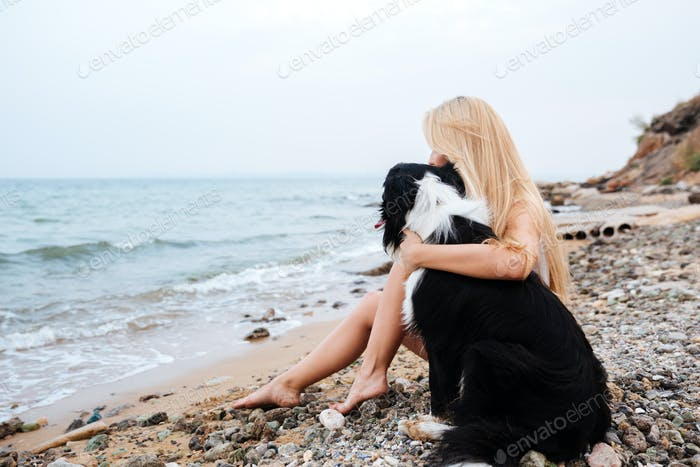 Woman sitting and hugging a dog on the beach