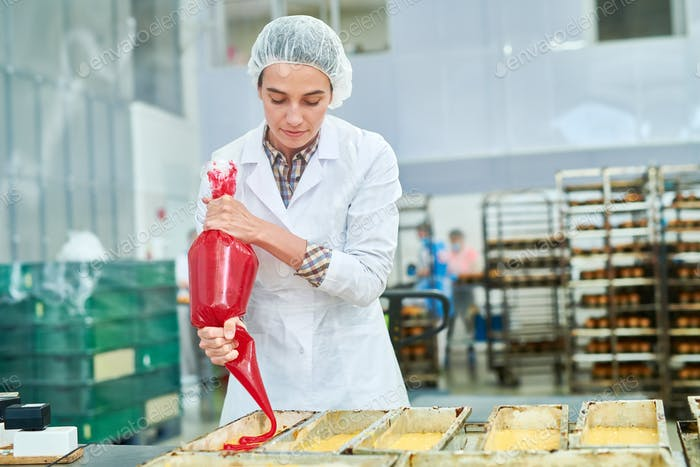 Confectionery factory worker using pastry bag