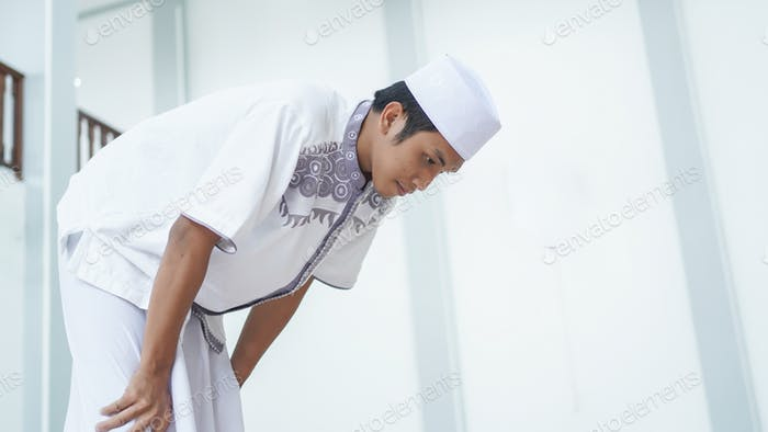 A portrait of an asian muslim man pray at mosque, the pray name is sholat, rukuk movement
