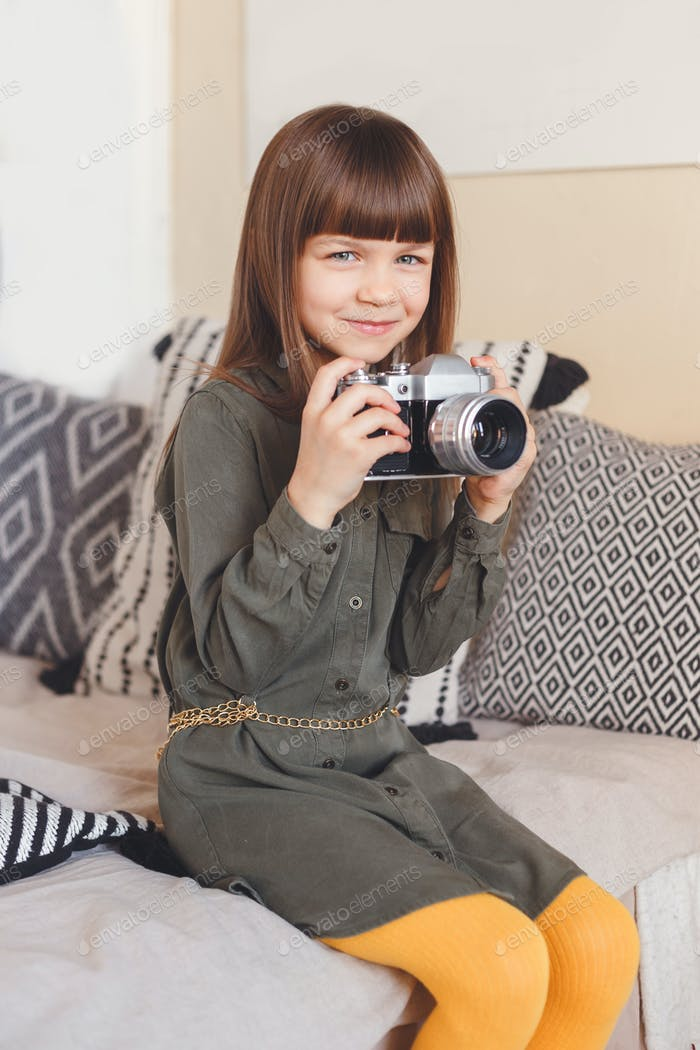 Little lady photographer with camera in room