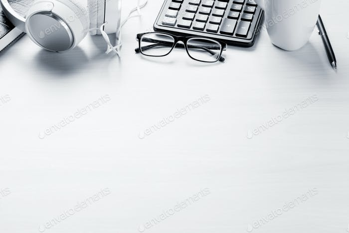 Office desk with coffee cup, notepad and headphones