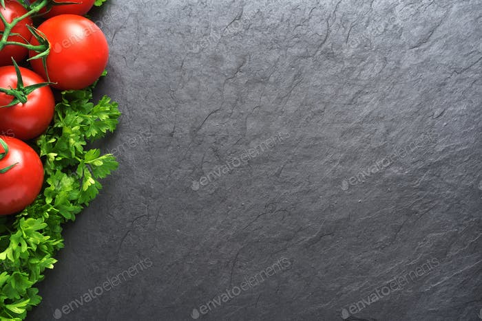 Red tomatoes and parsley on black slate with copy space