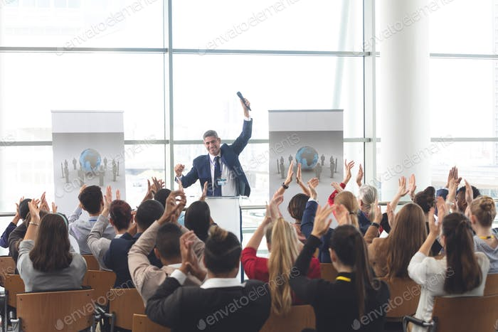 Diverse business people applauding a businessman at business seminar