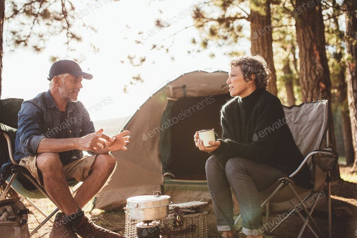 Mature man and woman sitting and talking at a campsite