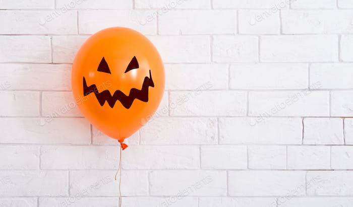 Conceptual Halloween balloon for party with scary smile