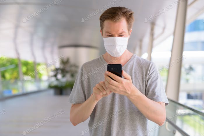 Young man with mask for protection from corona virus outbreak using phone in the city outdoors