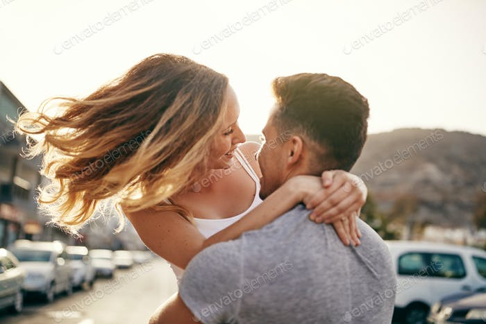 Laughing young couple hugging together on a street at sunset