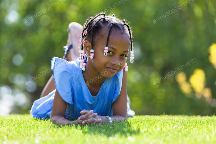 Al aire libre Vertical de un lindo joven negro chica acostado abajo en el g