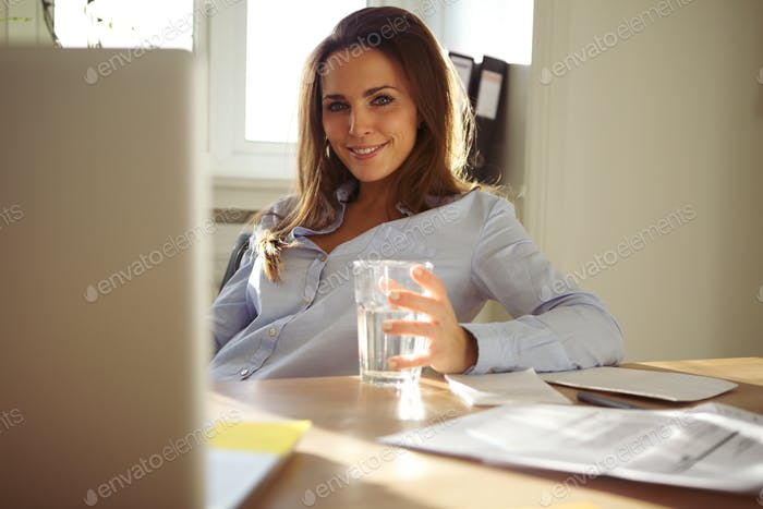 Happy young businesswoman sitting at her desk