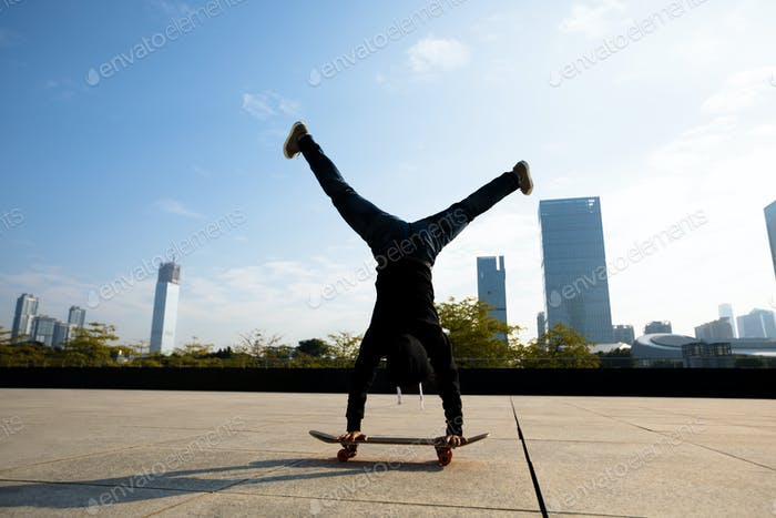 Skateboarder doing a handstand on skateboard in modern city