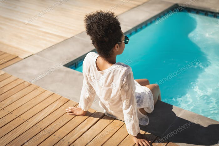 Young  woman with sunglasses sitting at poolside in backyard of home on a sunny day