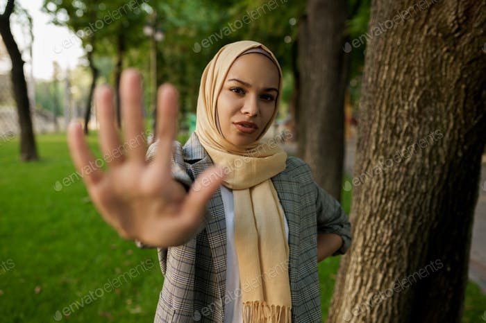 Arab girl in hijab shows her palm in summer park