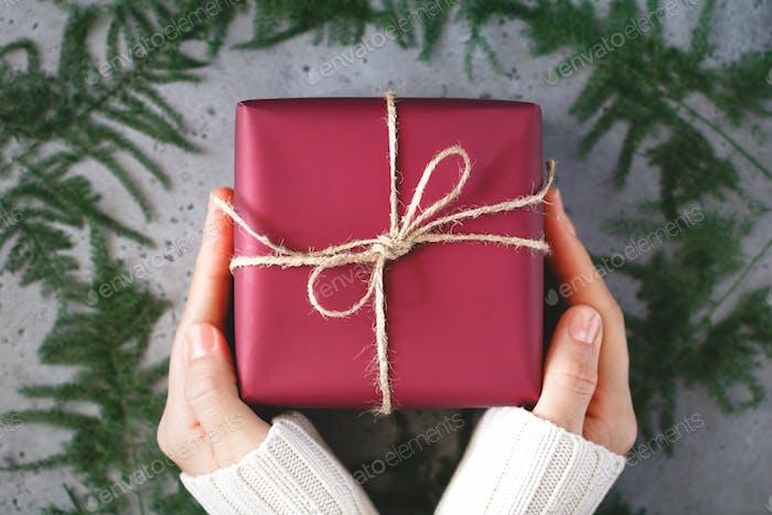 Mädchen Hände in einem Winter weißen warmen Pullover halten eine Weihnachtsgeschenk-Box