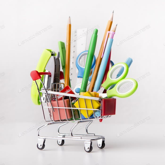 Close up of shopping cart with office supplies isolated on white