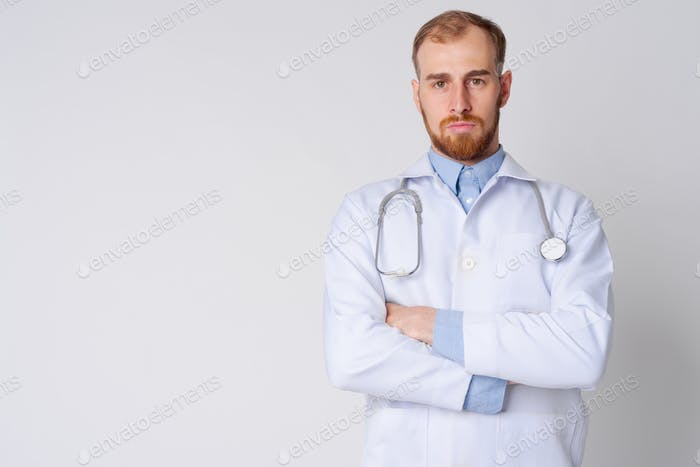 Portrait of young bearded man doctor with arms crossed