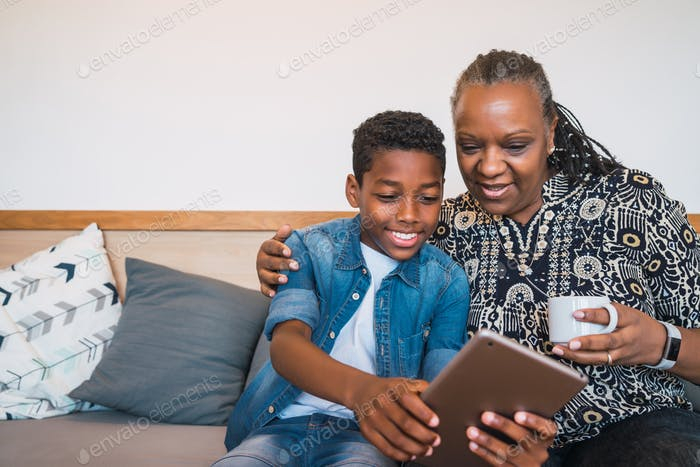 Grandmother and grandchild taking selfie with tablet.