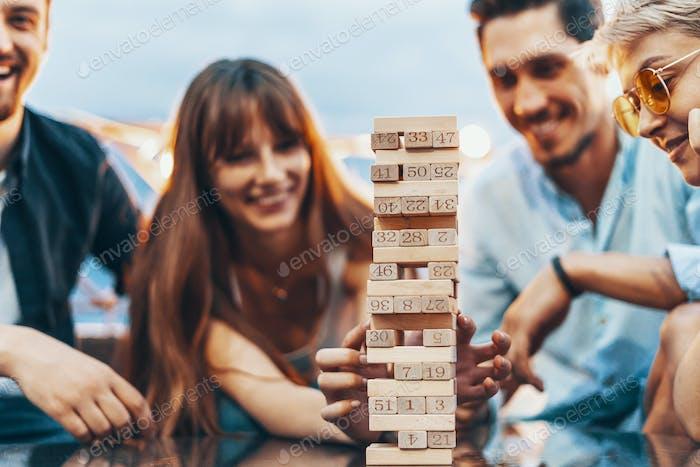 Компания молодых людей, играющих jenga