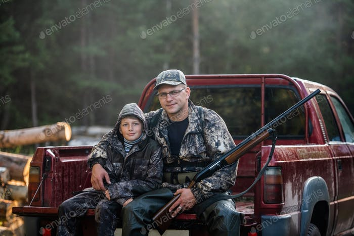 Father in a cap and his son sitting in a car after the hunt.